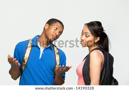 Two students wearing backpacks. He is shrugging his shoulders and she looks bored. Horizontally framed photograph. - stock photo