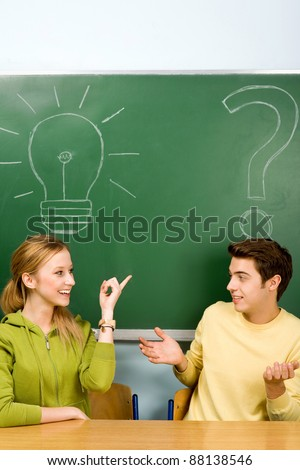 Two students with light bulb and question mark on chalkboard - stock photo