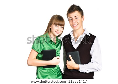 Two students with school books and tablets standing isolated on white background - stock photo