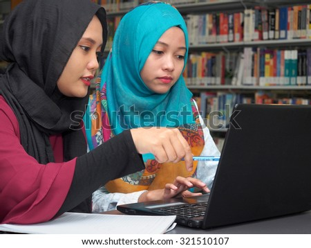 Two students working on a report in a library. - stock photo