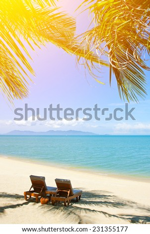 Two stylish beach chairs on idyllic tropical white sand beach. Shadow from the palm trees - stock photo