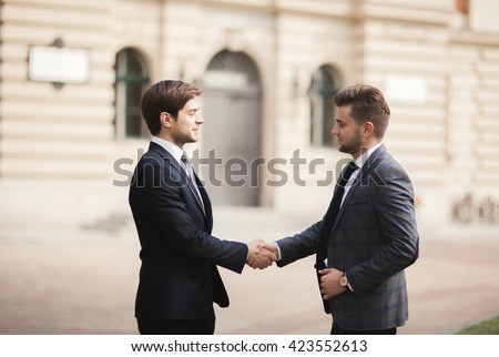 Two stylish businessmen shaking hands in suits - stock photo