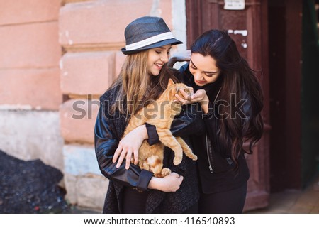 Two stylish street girls with a cat at the door - stock photo