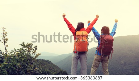 two successful backpacker enjoy the beautiful landscape at mountain peak - stock photo