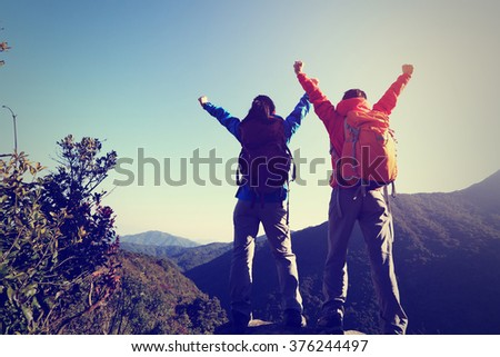 two successful backpacker open arms at mountain peak - stock photo