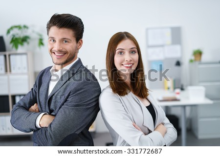 two successful business colleagues standing together with arms folded - stock photo