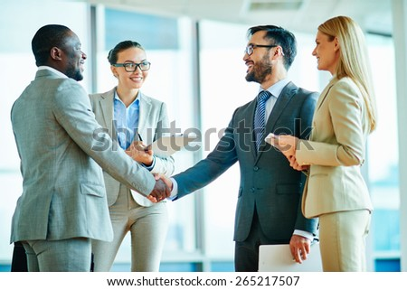Two successful businessmen handshaking with female colleagues near by - stock photo