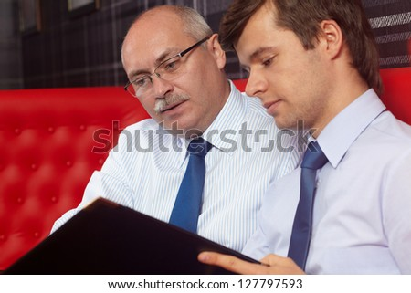 Two successful businessmen sitting together and talking about documents - stock photo