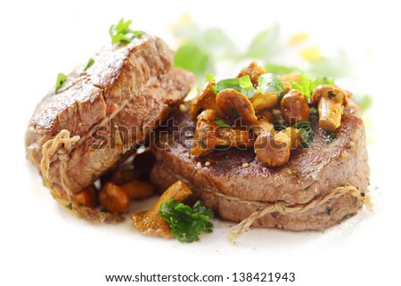 Two succulent thick grilled medallions of fillet steak tied with string and topped with fried mushrooms served on a white platter - stock photo