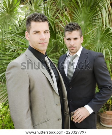 Two suit young elegant men posing in outdoors garden looking at the view, natural light. - stock photo