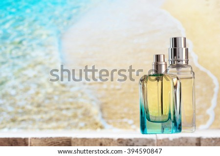 Two summer perfumes on white wooden table against defocused coastline. - stock photo