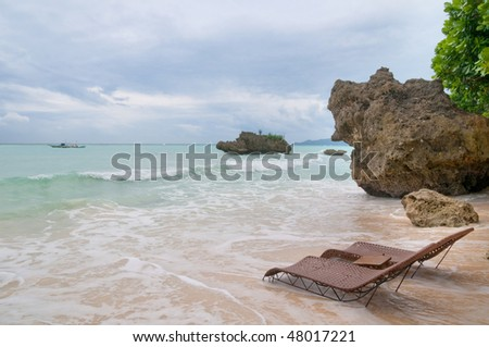 two sun beds on the seashore just before a storm - stock photo