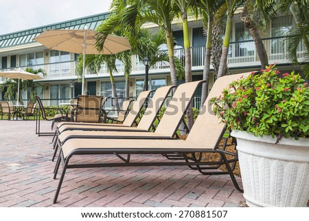 Two sun loungers by the pool  - stock photo
