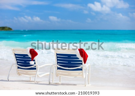 Two sun loungers with Santa hats on beautiful tropical beach with white sand and turquoise water, perfect Christmas vacation - stock photo