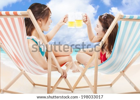 two sunshine girl holding beer cheers  on a beach chair - stock photo