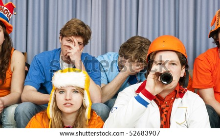 Two supporters looking in disbelief, surrounded by fans of the opposite team at home, watching television - stock photo