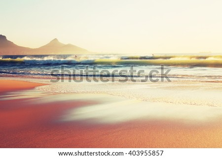 Two surfers enjoying the waves in Cape Town at sunset - stock photo
