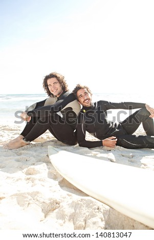 Two surfers friends sharing a surfing trip experience, laying down next to their surfing boards on a white sand beach with a sunny sky while on vacation and wearing specialist black neoprene suits. - stock photo