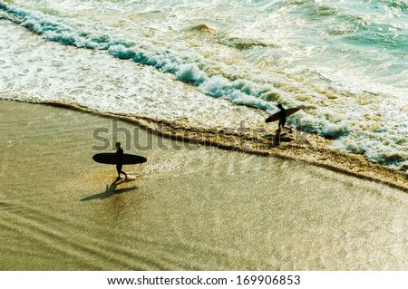 Two surfers going back to the beach - stock photo