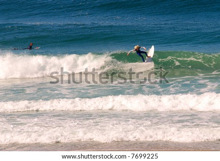 Two surfers in the water, one still upright - stock photo