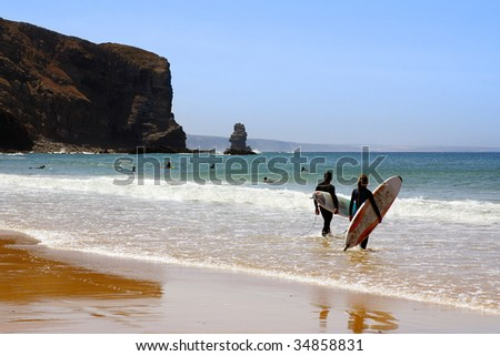 Two surfers ready to enter the sea in Arrifana Beach, Algarve Portugal - stock photo