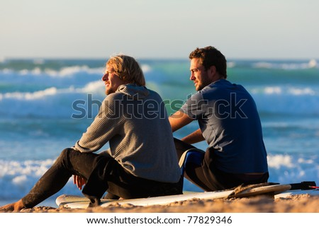 Two surfers sitting on their surf boards on the beach discussing the waves - stock photo