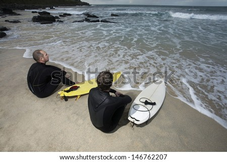 Two surfers with surfboards on beach looking at sea - stock photo