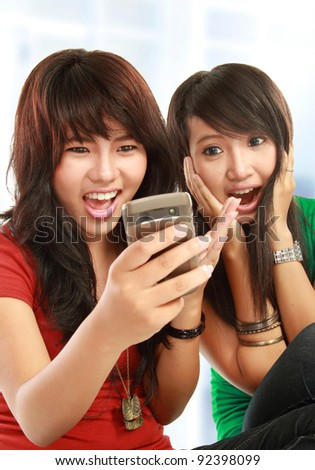 Two surprise girls reading text message in mobile phone - stock photo