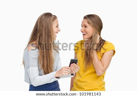 Two surprised young women holding a smartphone against white background - stock photo