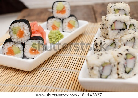 Two sushi sets on plates on a bamboo mat - stock photo