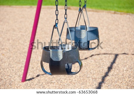 Two swings on a swing set used for younger children - stock photo