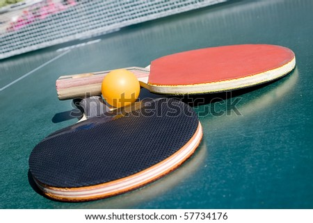 Two table tennis rackets and a ball on a green table with net - stock photo
