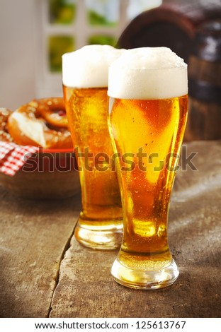 Two tall glasses of golden ale or beer with a good head of white froth on an old wooden kitchen table with a basket of rolls behind - stock photo