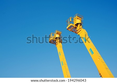 Two tall yellow lifts set against a blue sky. - stock photo