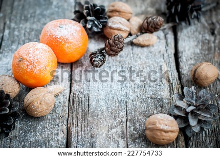 Two Tangerines, Pine cones, Walnuts, Candles and Almonds on Wooden Table, holiday card, selective focus - stock photo