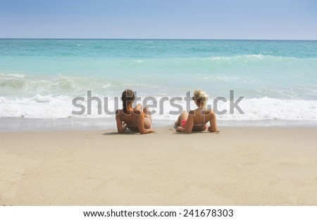 Two tanned women lying on the the beach - stock photo
