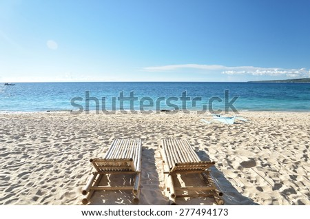 Two tanning beds at the tropical beach -- Tropical beach vacation and travel concept - stock photo