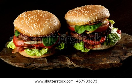 Two Tasty Hamburgers with Beef, Bacon, Lettuce, Tomatoes, Basil, Roasted Onion and Juicy Sauce on Sesame Buns on Stone Board closeup on Dark background - stock photo