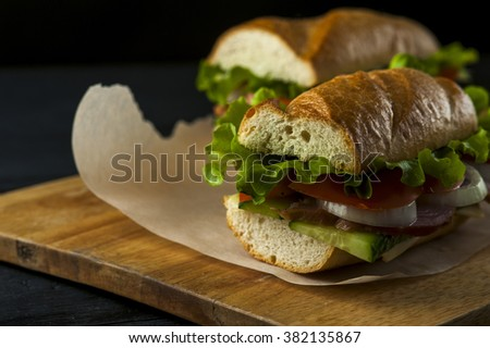 Two tasty sandwiches with ham and vegetables on baking paper on wooden table. Fast food - stock photo