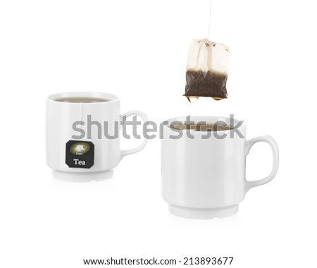 Two tea cups with tea bags, with one up with drops. - stock photo
