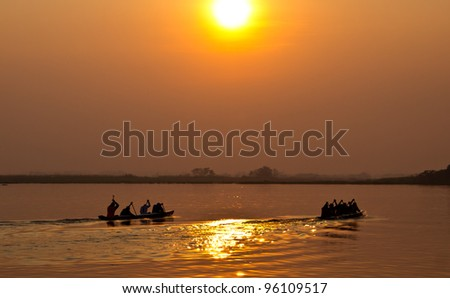 Two team of young mean in a row boat  against setting sun - stock photo