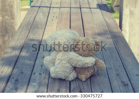 Two teddy bears hugging picnic in the park sit on wooden. vintage style. - stock photo