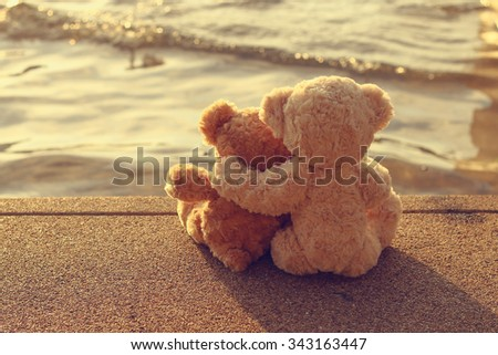Two teddy bears hugging sitting on the polished stone looking the sea sunrise. vintage style. - stock photo