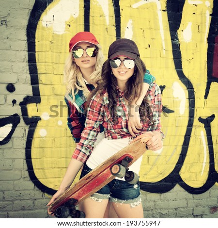 Two teen girl friends having fun together with skate board. Outdoors, urban lifestyle. Toned. - stock photo