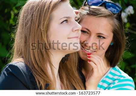 Two teen girl friends sharing secret happy smiling outdoors - stock photo
