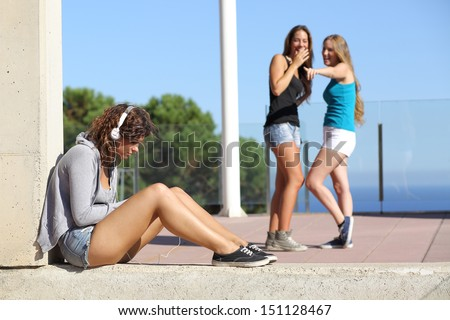 Two teen girls bullying and making fun and pointing another one  - stock photo