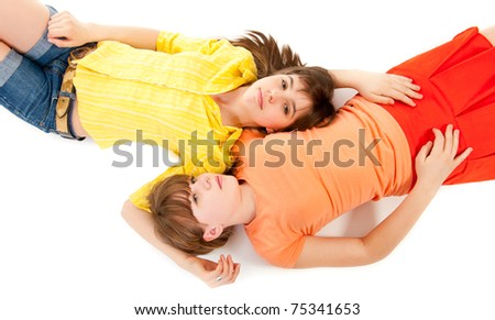 Two teen girls lie side by side isolated on white - stock photo