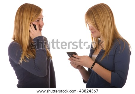 Two teen girls on their cell phone, talking and texting. - stock photo