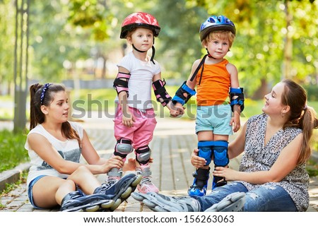 Two teen girls sit on ground and support kids in rollers who stand holding hands - stock photo