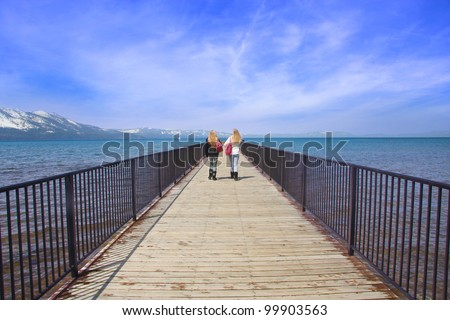 Two teen girls walking toward a view on a pier over a lake. - stock photo